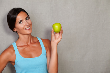 sport wear: Healthy lady holding apple and showing toothy smile while looking at camera in sport wear against grey texture background