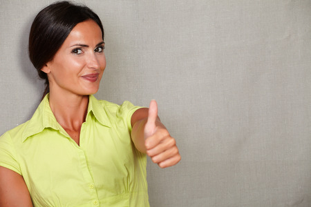 hair back: Happy adult female with thumb up and smiling satisfied while looking at camera and wearing green blouse and hair back on grey texture background Stock Photo