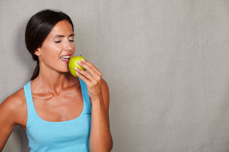 caucasian ethnicity: Caucasian ethnicity woman with eyes closed while eating apple in gym clothing against grey texture background