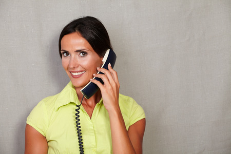 hair back: Beautiful brunette lady holding phone and smiling with toothy smile on green blouse with hair back while looking at camera on grey texture background