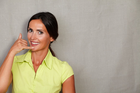 hair back: Caucasian ethnicity woman gesturing a phone call and looking at camera in green blouse and hair back on grey texture background Stock Photo