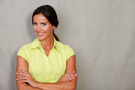 hair back: Confident adult lady in casual clothing and hair back while smiling and crossed her arms and looking at camera on grey texture background