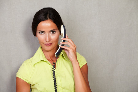 caucasian ethnicity: Caucasian ethnicity adult lady in casual clothing holding phone while looking at camera disappointed on grey texture background