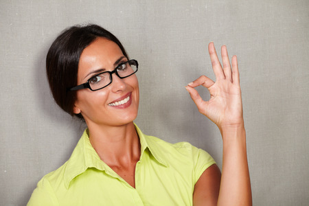 perfect sign: Happy lady congratulating with perfect sign and smiling satisfied while wearing glasses and green blouse and looking at camera on grey texture background