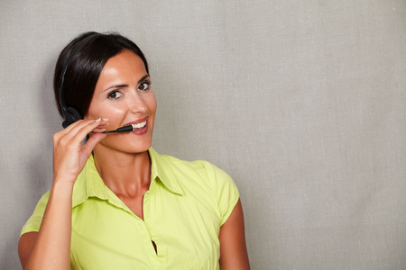 charismatic: Charismatic call center lady on headset while talking and looking at camera on grey texture background