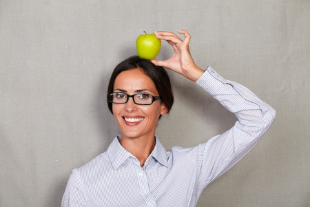 button down shirt: Young businesswoman with glasses holding apple on head while smiling and looking at camera in button down shirt against grey texture background