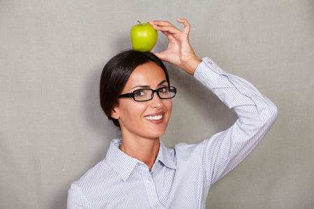 formal wear: Smiling brunette lady wearing glasses and holding apple on head while looking at camera in formal wear on grey texture background