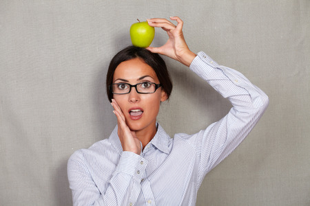 formal clothing: Shocked well-dressed female with apple on head and hand on face while looking at camera in glasses and formal clothing on grey texture background Stock Photo