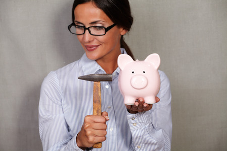 Straight hair female holding hammer and breaking piggy bank in formal wear and glasses on grey texture background