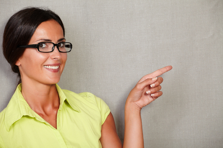 hair back: Female with glasses pointing to her left and smiling with toothy smile while looking at camera in casual clothing and hair back on grey texture background