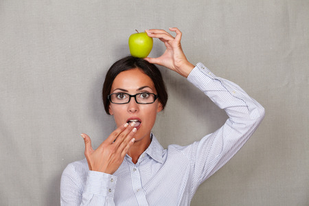 formal wear: Shocked lady with apple on head and open mouth while looking at camera shocked and with hand to mouth in formal wear and glasses on grey texture background Stock Photo
