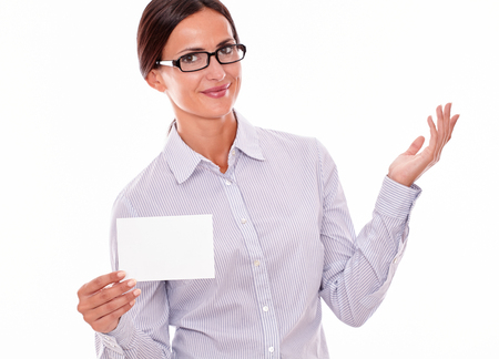 tied down: Smiling brunette businesswoman with glasses, wearing her long hair tied back, and a button down shirt, gesturing, holding a blank copy space in one hand on a white background