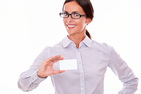 button down shirt: Smiling brunette businesswoman with glasses, wearing her long hair tied back, and a button down shirt, holding a blank visit card in one hand on a white background