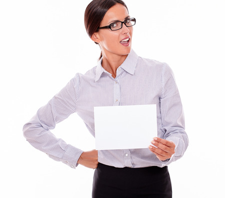 tied down: Shocked brunette businesswoman with glasses, wearing her long hair tied back, and a button down shirt, holding a blank signboard in one hand, the other hand on her hip
