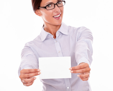 button down shirt: Smiling brunette businesswoman with glasses, wearing her long hair tied back, and a button down shirt, looking excited, holding a blank copy space with both hands in front of her