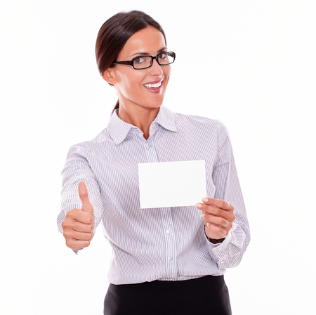 hair tied back: Satisfied brunette businesswoman with glasses, wearing her long hair tied back, and a button down shirt, holding a blank copy space in one hand, gesturing thumbs up with the other hand Stock Photo