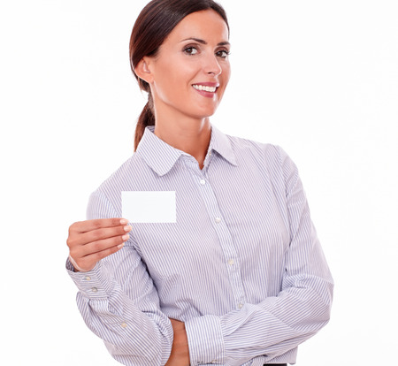 button down shirt: Attractive brunette businesswoman with a toothy smile, wearing a button down shirt, looking at the camera with her long hair tied back, holding a blank visit card with one hand on a white background