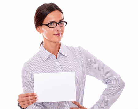 impassive: Unsatisfied brunette businesswoman with glasses, wearing her long hair tied back, and a button down shirt, holding a blank signboard in one hand, and the other hand on her hip