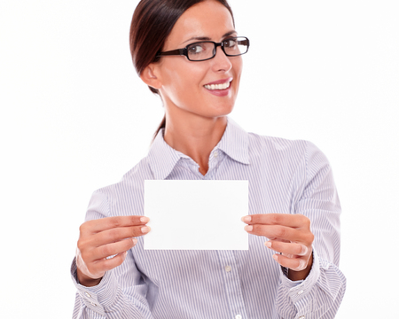 button down shirt: Happy brunette businesswoman with glasses, wearing her long hair tied back, and a button down shirt, looking excited, holding a blank copy space with both hands in front of her