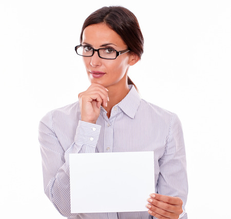 impassive: Indifferent brunette businesswoman with glasses, wearing her long hair tied back, and a button down shirt, holding a blank signboard in one hand, and the other hand on her chin