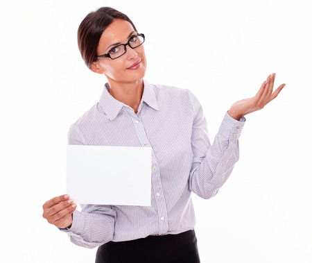 impassive: Impassive brunette businesswoman with glasses, wearing her long hair tied back, and a button down shirt, holding a blank signboard in one hand, gesturing indifference with the other hand