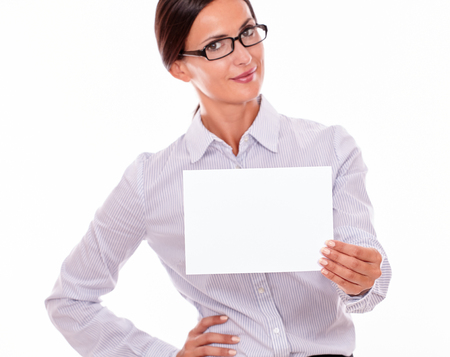 button down shirt: Smiling brunette businesswoman with glasses, wearing her long hair tied back, and a button down shirt, holding a blank signboard in one hand, and the other hand on her hip