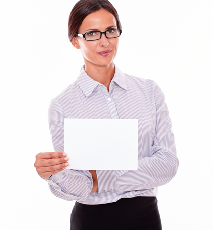 button down shirt: Impassive brunette businesswoman with glasses, wearing her long hair tied back, and a button down shirt, holding a blank signboard in one hand, and pointing the other arm folded across her body