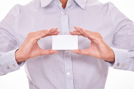 button down shirt: Cropped businesswoman wearing a striped button down shirt, holding a blank visit card with both hands Stock Photo