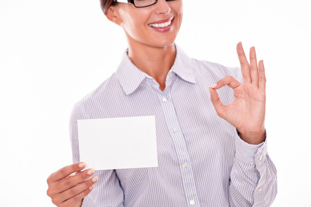 button down shirt: Smiling brunette businesswoman with glasses, wearing her long hair tied back, and a button down shirt, holding a blank copy space in one hand gesturing a perfect sign with the other hand