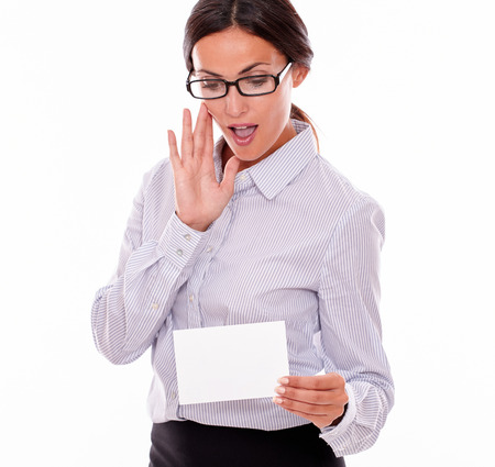 tied down: Surprised brunette businesswoman with glasses, open mouth, wearing her long hair tied back, and a button down shirt, holding a blank copy space in one hand gesturing her surprise with the other hand