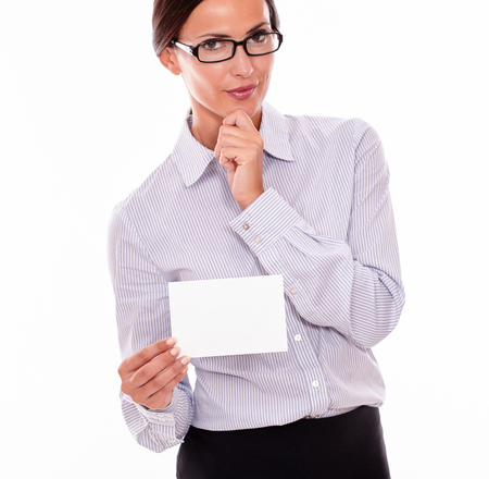 button down shirt: Pensive brunette businesswoman with glasses, wearing her long hair tied back, and a button down shirt, holding a blank copy space in one hand holding her chin with the other hand