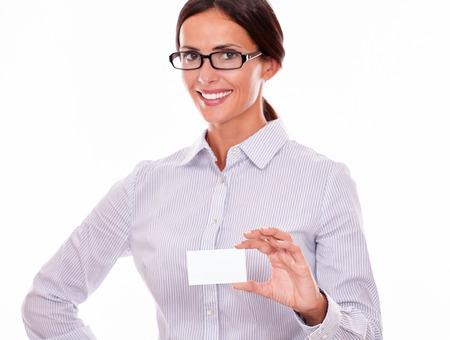 button down shirt: Smiling brunette businesswoman, wearing her long hair tied back, and a button down shirt and glasses, holding a blank visit card in one hand on a white background