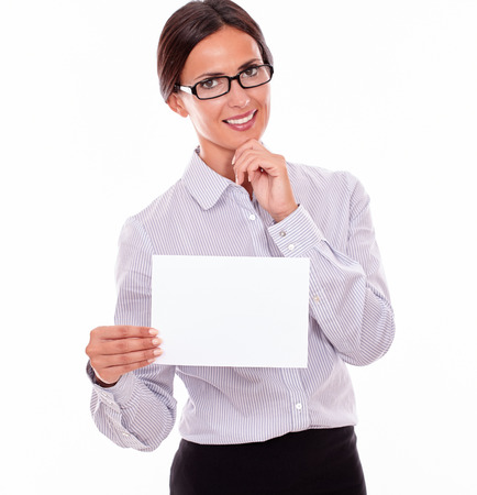 tied down: Excited brunette businesswoman with glasses, wearing her long hair tied back, and a button down shirt, holding a blank signboard in one hand, and pointing at it with the other hand Stock Photo