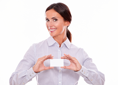 back straight: Brunette businesswoman, with toothy smile, wearing a button down shirt and her straight long hair back, showing a blank visit card
