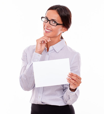 button down shirt: Excited brunette businesswoman with glasses, wearing her long hair tied back, and a button down shirt, holding a blank signboard in one hand, and with the other hand on her chin