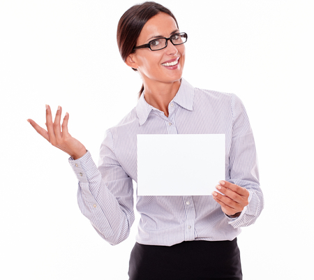 button down shirt: Excited brunette businesswoman with glasses, wearing her long hair tied back, and a button down shirt, holding a blank signboard in one hand, gesturing with the other hand