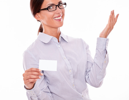 hair tied back: Satisfied brunette businesswoman with glasses, wearing her long hair tied back, and a button down shirt, holding a blank visit card with one hand and looking at the camera on a white background