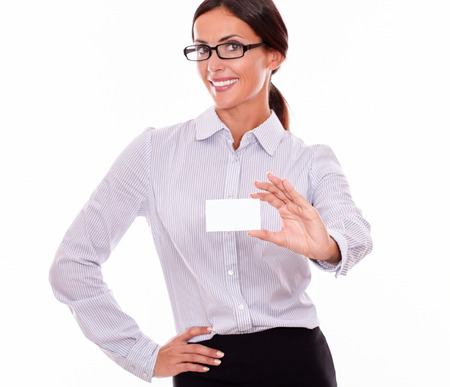 attractiveness: Smiling brunette businesswoman, wearing her long hair tied back, and a button down shirt and glasses, holding a blank visit card in one hand and her other hand on her hip, on a white background Stock Photo