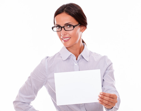 indifferent: Indifferent, smiling brunette businesswoman with glasses, wearing her long hair tied back, and a button down shirt, holding a blank signboard in one hand, and the other hand on her hip Stock Photo