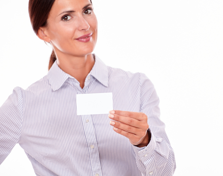 hair tied back: Smiling attractive, brunette businesswoman, looking at the camera with her long hair tied back, wearing a button down shirt, holding a blank visit card with one hand with a white background