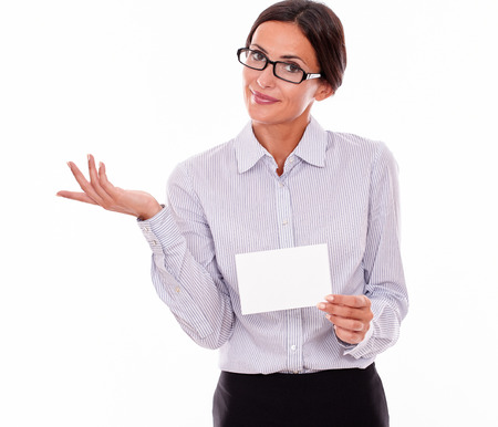 impassive: Indifferent brunette businesswoman with glasses, wearing her long hair tied back, and a button down shirt, holding a blank copy space in one hand, gesturing indifference with the other hand
