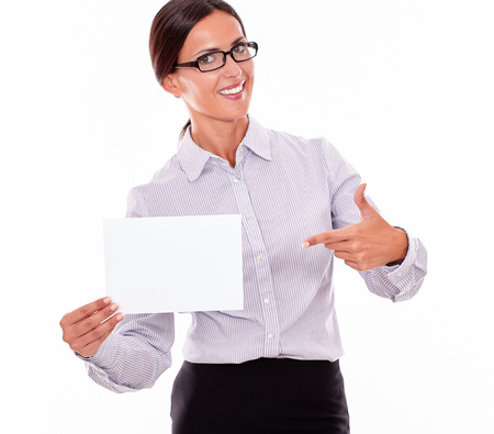 hair tied back: Excited brunette businesswoman with glasses, wearing her long hair tied back, and a button down shirt, holding a blank signboard in one hand, and pointing at it with the other hand Stock Photo