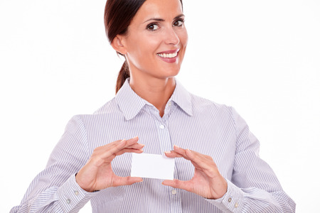 button down shirt: Smiling brunette businesswoman, wearing a button down shirt, holding a blank visit card with a white background