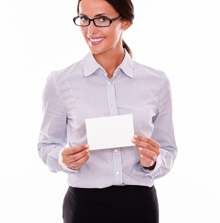 button down shirt: Smiling brunette businesswoman with glasses, wearing her long hair tied back, and a button down shirt, holding a blank copy space with both hands in front of her on a white background