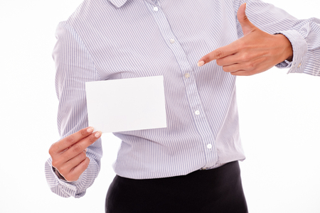button down shirt: Cropped businesswoman, wearing a button down shirt, holding a blank copy space in one hand pointing at the copy space with the other hand Stock Photo