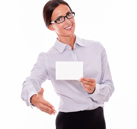 attractiveness: Smiling brunette businesswoman with glasses, wearing her long hair tied back, and a button down shirt, holding a blank copy space in one hand, with the other hand out in a greeting gesture