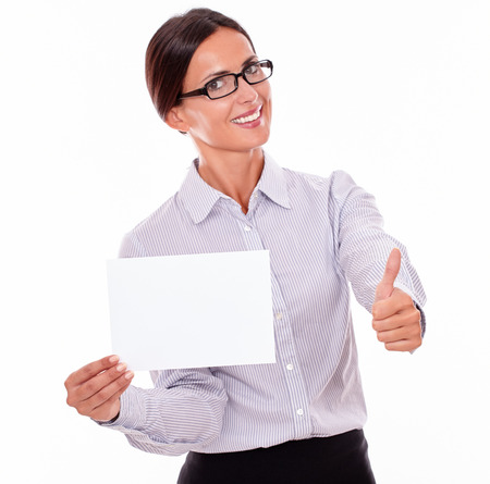 hair tied back: Indifferent brunette businesswoman with glasses, wearing her long hair tied back, and a button down shirt, holding a blank copy space in one hand, gesturing thumbs up with the other hand Stock Photo
