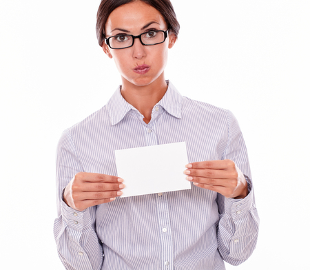 hair tied back: Stressed brunette businesswoman with glasses, wearing her long hair tied back, and a button down shirt, holding a blank copy space with both hands in front of her on a white background Stock Photo