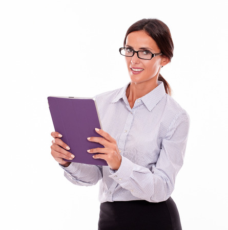 hair tied back: Smiling happy brunette businesswoman with glasses carrying a tablet, wearing her straight hair tied back and a button down shirt while looking at the camera on a white background Stock Photo