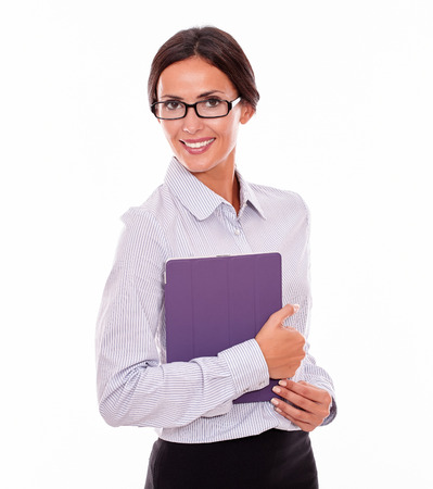hair tied back: Smiling brunette businesswoman with glasses carrying a tablet, wearing her straight hair tied back and a button down shirt, looking at the camera, on a white background